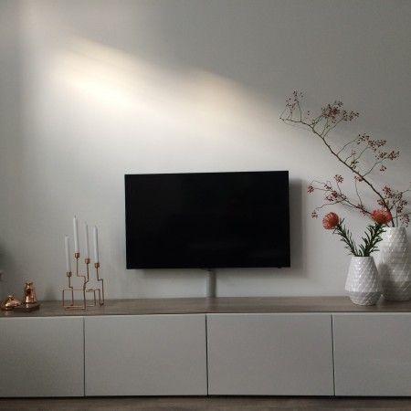 Tover een wit televisiemeubel weg met een witte muur. Laat je accessoires opvallen. Bekijk meer wooninspiratie op vtwonen.nl.