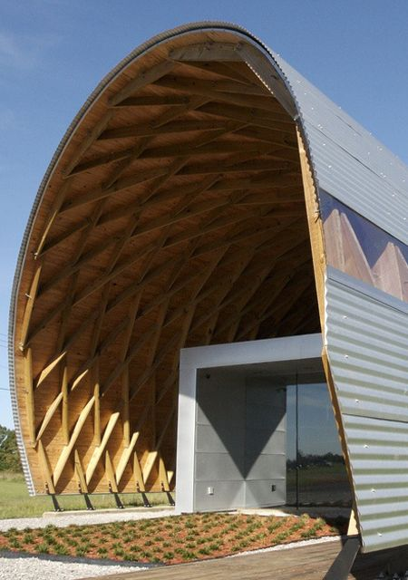 A repeating diamond structure called a lamella acts as both roof and wall for the dog pound. The simple look of the form from the exterior hides the exposed structure seen within. The identical 2×8 joists were precut and curved by a jig, and a simple pin connection was used to hold the pieces in place. Taking a page from the prefabrication handbook, the students cut down on overall material costs by creating a standard, and repeat the process over and again.