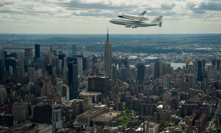 Space shuttle Enterprise, mounted atop a NASA 747 Shuttle Carrier Aircraft, flies by the Empire State Building.