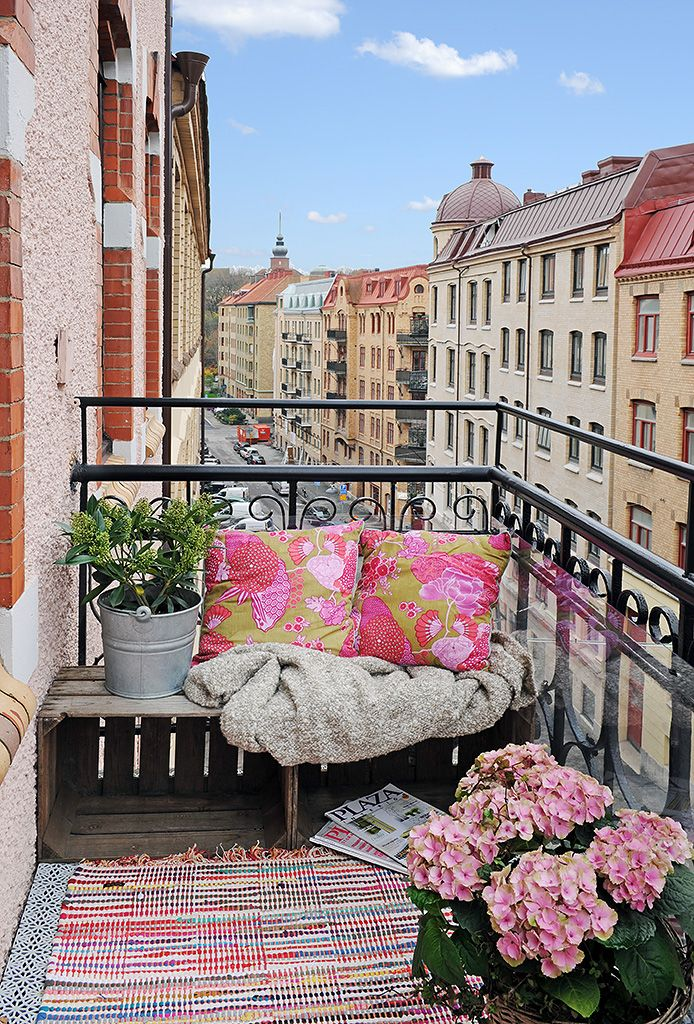 Balcony bench of crates, comfy pillows & throw, bucket & basket with plants