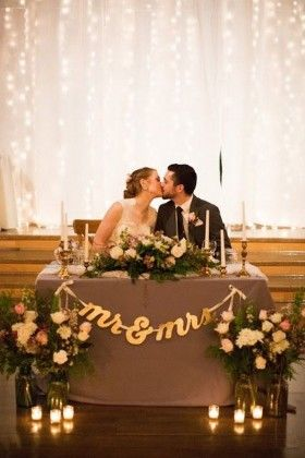 Mr & Mrs sweetheart table with twinkle light backdrop and bride and groom kiss
