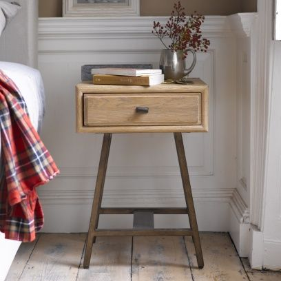 CAMPAIGN BEDSIDE TABLE Inspired by a 1940s sideboard we saw in a Parisian market. The oak goes through a 15-step process to obtain a gorgeous hand-finished texture. With vintage bronze finish metal legs.