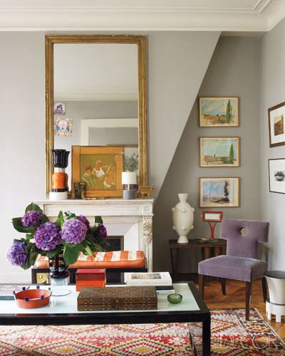 layered, eclectic room. purple velvet chair, orange striped bench, mirror with picture in front. love.