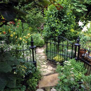 Garden Gates: Work with Your Landscape...   This simple wrought-iron gate looks right at home among a bed of flowering perennials and a flagstone path. The simplicity is effective: A larger gate might distract from the natural feel of the garden.