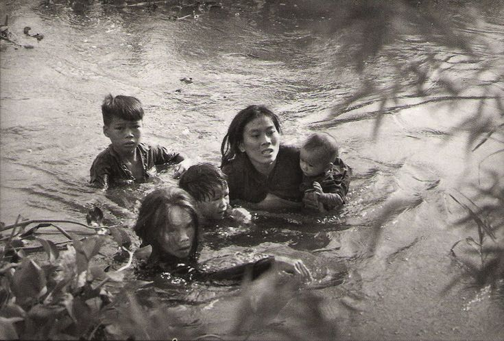 'Mother and children wade across river to escape U.S. bombing. Qui Nhon, South Vietnam' September 1965