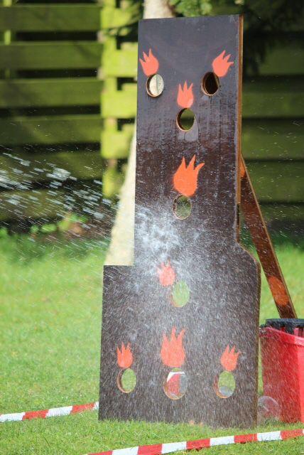 Zelfgemaakte toren om te blussen. Achter de gaten staan bekertjes gevuld met water.kinderen gaan lekker met de tuinslang aan de gang. Was een groot succes!