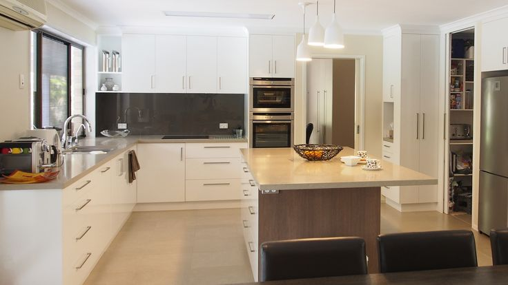 Custom made cabinets in Polytec Classic White Sheen with Laminex Amari Oak feature colour on island back.  40mm Caesarstone Shitake bench top with undermount sink  Features BLUM tandembox soft close drawers, walk in pantry with cavity slider door and charging station