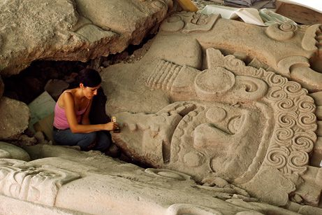An archaeologist works on a stone monolith at the Templo Mayor (Great Temple) site in Mexico City.  The skeleton of a richly decorated canine and several unbroken plaster seals add to clues that the site could be the only known tomb of an Aztec king, researchers said in June 2009.