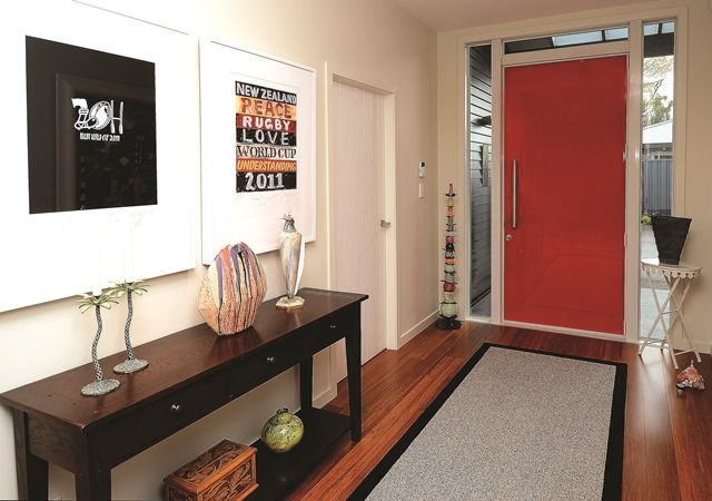 The home's red front door leads into a formal entrance showcasing some of the owner's favourite artwork.