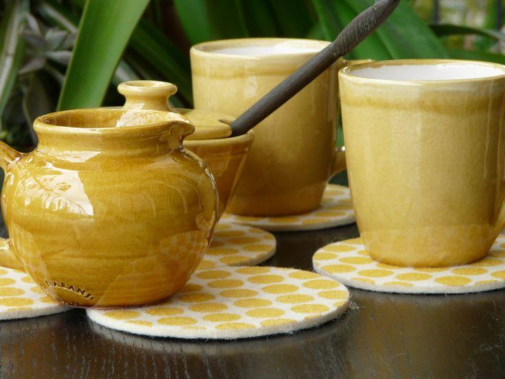 Mugs, lechera y azucarera de cerámica esmaltada artesanal (varios colores disponibles). Cucharas de madera de palo santo talladas a mano. Posa-vaso de fieltro estampado con tintas al agua. (Obra Inspiración Sustentable)