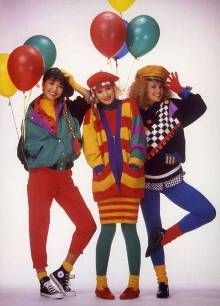 throwback outfits, three smiling young women in bright clothes, red pants green and blue leggings, yellow and red striped cardigan, green jacket yellow socks and colorful balloons