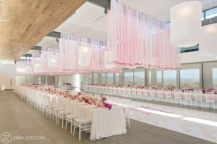 Pink & White Wedding Reception decor. Pink & White flowers in the centre of the long tables and strands of ribbon creating a curtain effect over the dance floor.