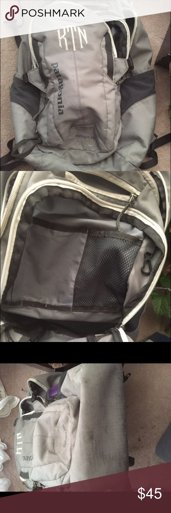 Grey Patagonia Refugio 28L backpack This is a worn, pre-monogrammed Patagonia Refugio 28L backpack! The colors are a light heather gray, with dark grey and white accents. Some of the white accents have discolored due to usage. This backpack has seen its use but is still in great shape! It has some stains, mostly on the bottom of the bag and on the bottom front of the back that could probably be fixed with dry cleaning! There is an ink stain on one of the inside pockets but won't be noticed…
