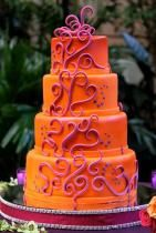 Four tier round orange wedding cake with purple wave decor.JPG