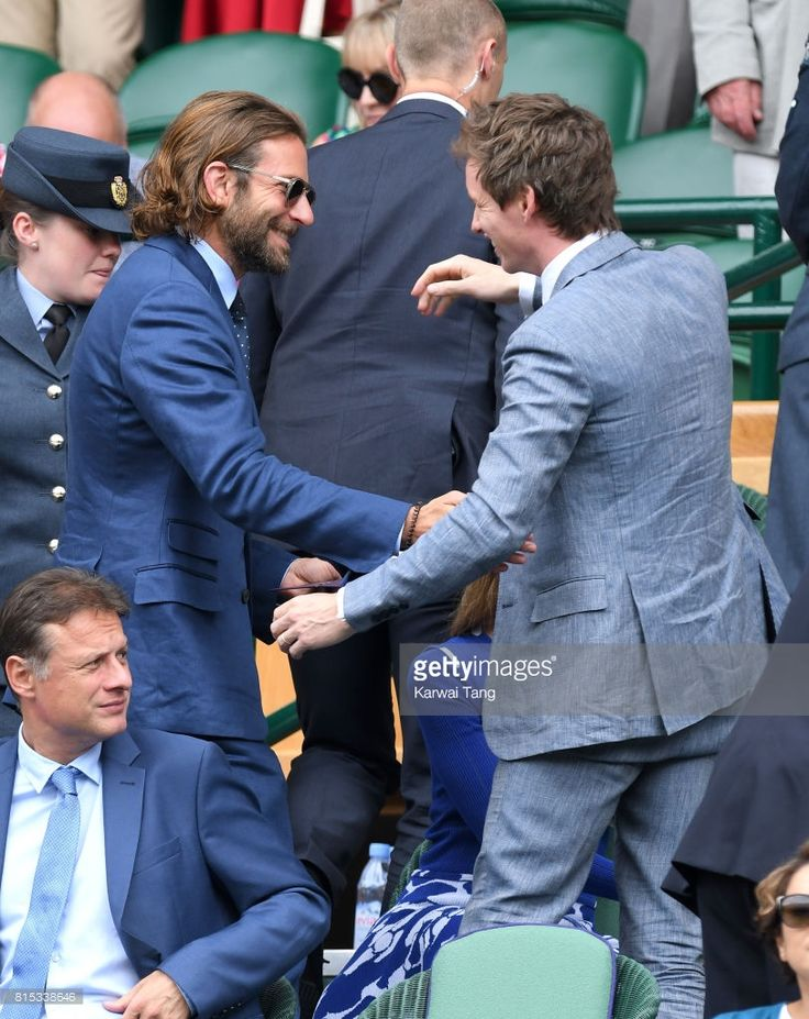 Bradley Cooper and Eddie Redmayne greet each other as they attend day 13 of Wimbledon 2017 on July 16, 2017 in London, England.