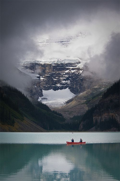 A Break in the Clouds - Canoeing on beautiful Lake Louise in Alberta Canada .. Photo by Jeff Pang