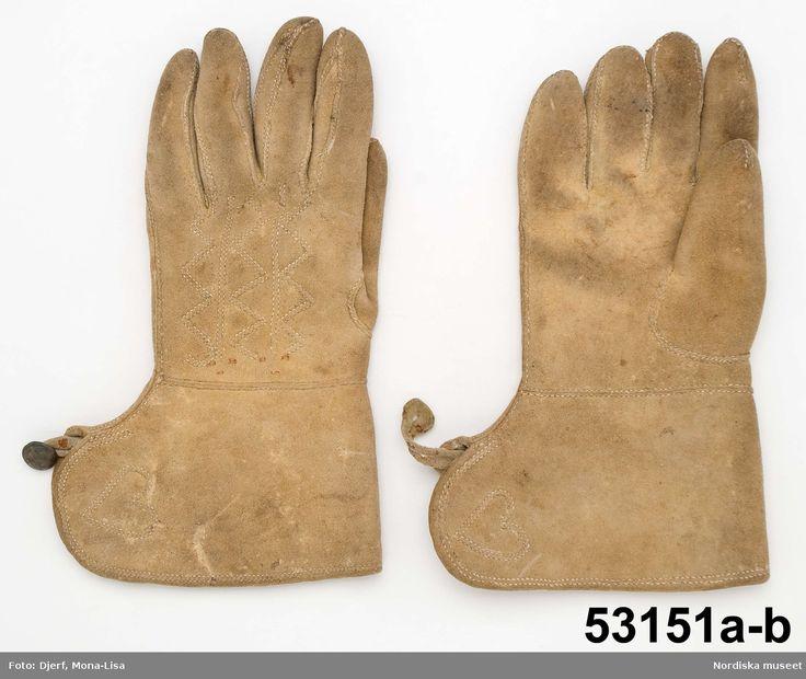 1 par kraftiga kraghandskar av grågult tjockt sämskat älgskinn. På kragen laskade hjärtan vid sprundet. På handens ovansida laskade sömmar i sicksack.  Handskarna handsydda. På den ena ögla av skinn och på den andra en slät knapp på skinnbit så att handskarna kan knäppas ihop med varandra.  Bars som brudgumshandskar sannolikt i slutet på 1700-talet.   Liknande kraghandskar bars av brudgummar även i delar av Småland och Hälsingland vid den tiden. Påverkade av 1700-talets uniformshandskar…