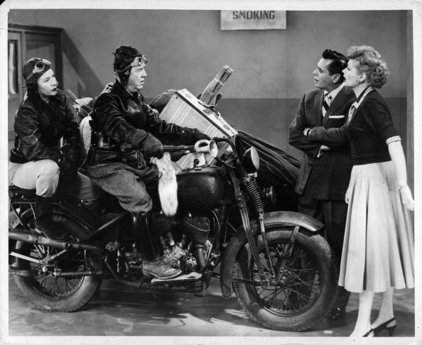 Vivian Vance and Bill Frawley ride in on a motorcycle in front of a dismayed Desi Arnaz and Lucille Ball in the television series 'I Love Lucy' 1951