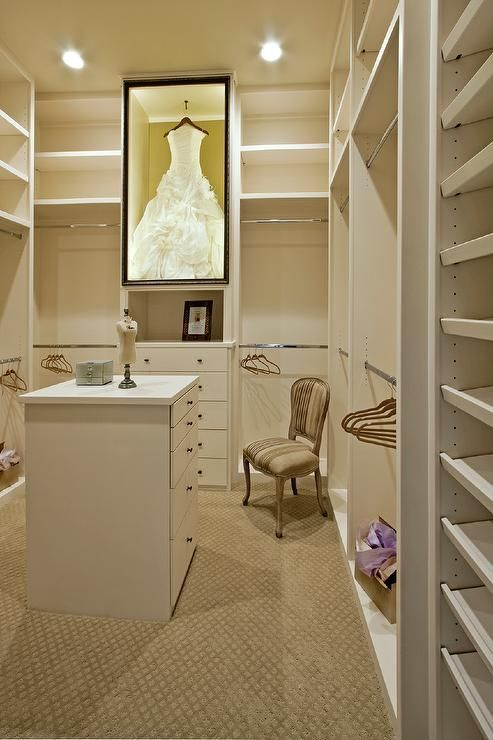 Large white walk in closet fitted with built in modular shelves boasts a custom lit, black framed, glass, wedding dress display case mounted over a built in dresser and flanked by stainless steel clothing rails illuminated by recessed lighting.