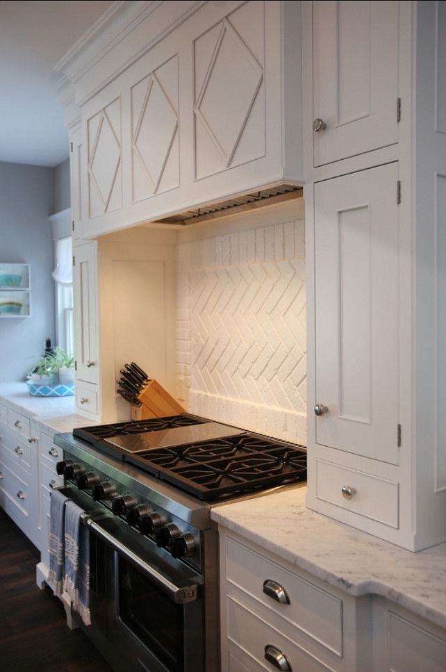 Exquisite Kitchen Features A White Range Hood Accented With Diamond Trim Molding Over White Brick Herringbone Cooktop Backsplash Over Stainless Steel Stove