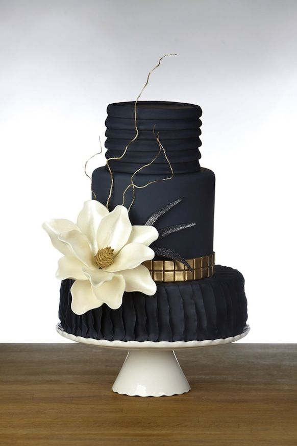 Midnight blue fondant wedding cake decorated with a large ivory magnolia, shimmering fillers and gold trimming.  An unconventional dark design that is elegant and sohisticated.
