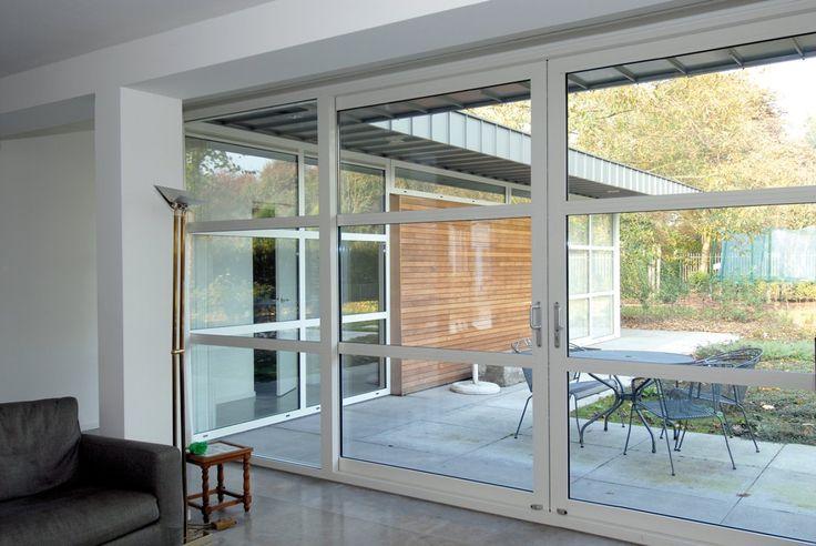 Deze op maat gemaakte schuifpui van wit aluminium sluit fraai aan op modern terras.