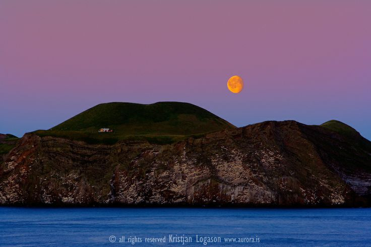 Moon over the island bjarnarey part of vestmanna islands in Iceland