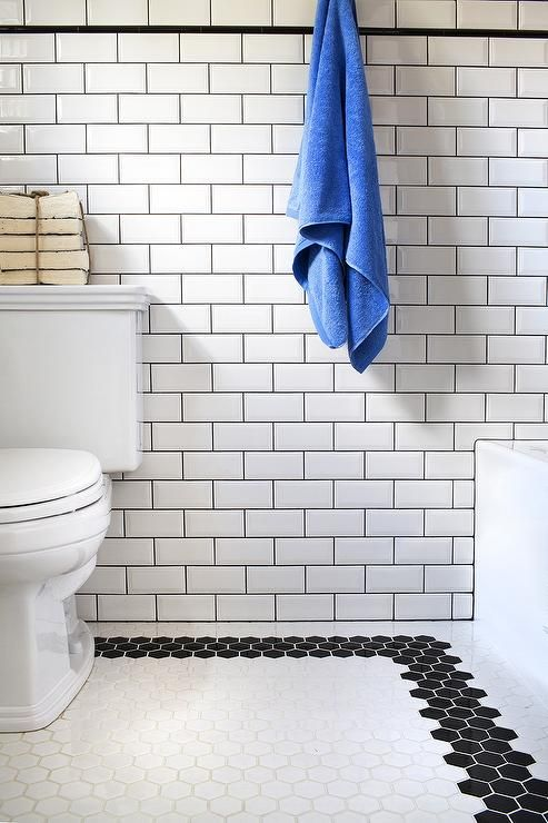 Fabulous bathroom features walls clad in white beveled subway tiles accented with black grout alongside a black pencil border tiles.