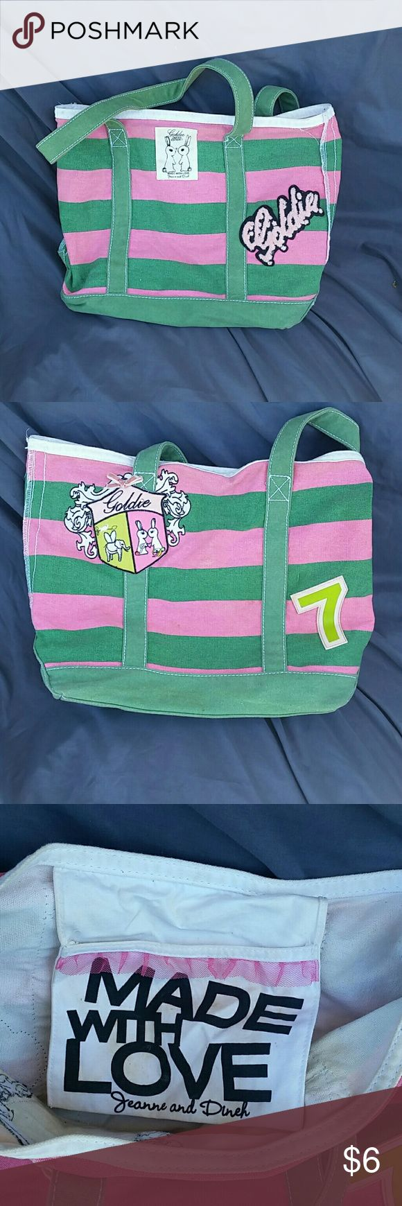 Goldie Green and Pink Striped Canvas Bag Goldie by Jean ne and Dineh Canvas Bag. This is pink and green striped. There is different patches on this and little rhinestones. Canvas straps in green. Off white inside with some staining. Outside no flaws. Pocket on the inside with pink tulle ruffle. Bags Shoulder Bags