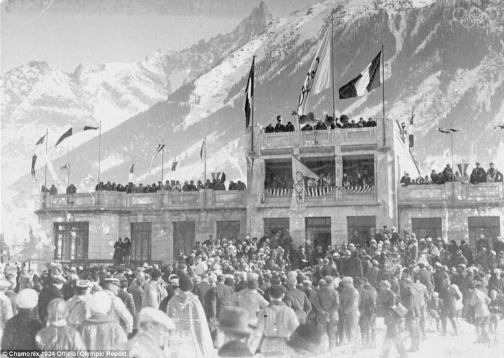 Spectators gathering around the official stand, with the Alps in the background.