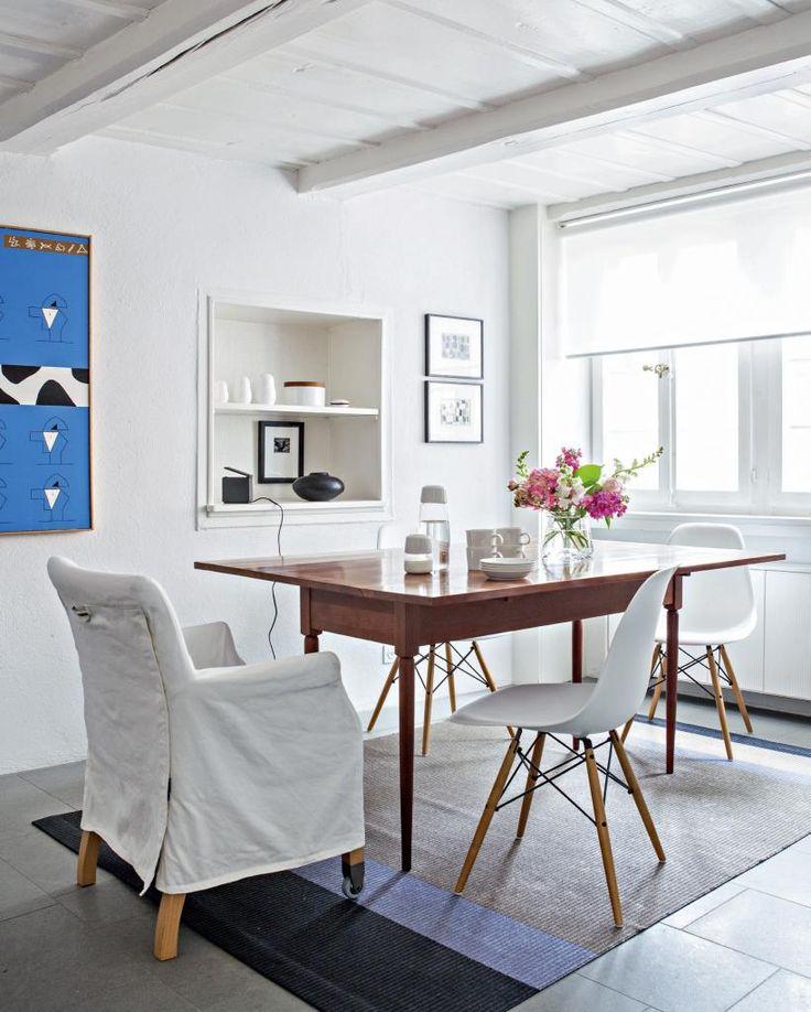 Italialaisen  De Padovan Shaker-pöydän alla on Woodnotesin matto. Pöydän ympärillä Flexformin Pausa-tuoli sekä Ray ja Charles Eamesin valkoiset DSW-tuolit. | Vanhan kaupungin helmi | Koti ja keittiö | Jutta Ylä-Mononen | Kuva Kirsi-Marja Savola