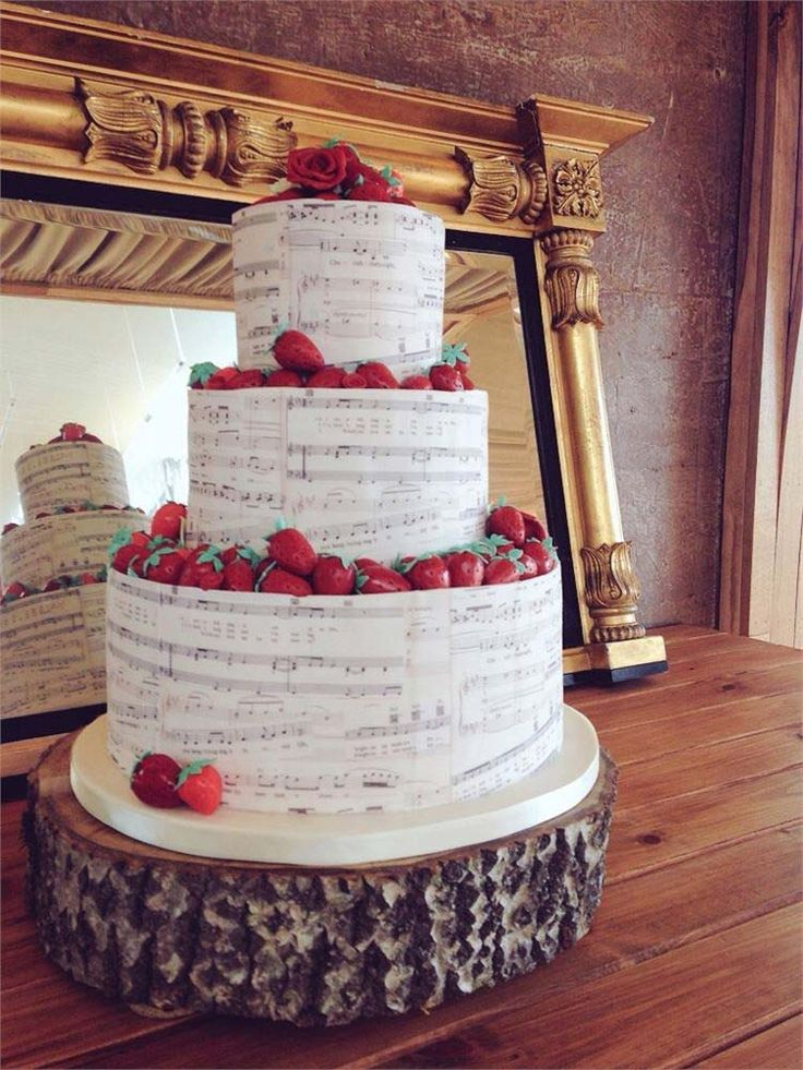 Musical themed artsy wedding cake..Music Themed  This song sheet cake would make a sophisticated and refined centrepiece at your reception! Decorated with fresh strawberries, this music themed wedding cake from The Vanilla Pod Bakery is a must for musical couples. To make it really personal, you could request for the music sheets to include your favourite song!