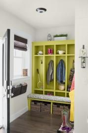 """The mudroom's citrusy-green built-in cubbies and cushioned bench say """"Stop and stow your stuff!"""" to anyone coming or going. Baskets, hooks, and wall-hung organizers offer a place for everything by the back door. Built-ins: Cubbies; BOJ Construction Paint: Parachute; Olympic Bench cushion: Rafiki/Graphite; Smith & Noble Upholstery: Chris Upholstery Window treatment: Natural woven shade; Smith & Noble Accessories: Industrial mailbox by Linon; Hayneedle.com Hooks: Iro..."""