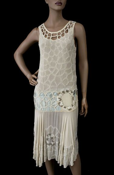 Beaded 1920s flapper dress, made from cream colored silk chiffon, the torso is embellished with a cobweb style design of white glass beads. The design's fluid quality accentuates female curves. The neckline is bordered with open work. The dress has a celadon green ribbon cummerbund at the hipline. The hipline medallion glitters with rhinestones and silver-lined crystal beads. The bias cut skirt, which drapes in soft folds, has a wide beaded hem border in the cobweb pattern with more…
