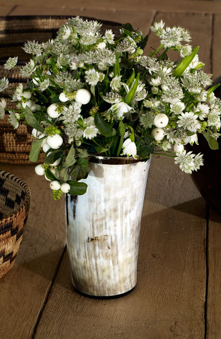 A Ralph Lauren Home ski-chalet bouquet of winter berries and morning drops in a horn vase