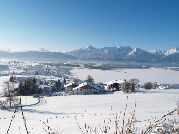 Winterpanorama in Hopfen am See in den Bayerischen Alpen. Blick auf das Hotel Eggensberger, den Hopfensee und die Berge.