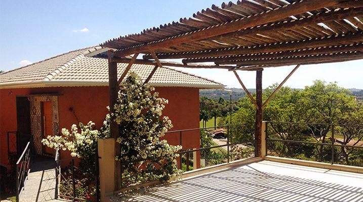 Entrada principal da Residencia com um patchwork de ladrilhos hidraulicos, pintura das paredes feita a base de pó de terra e a garagem feita de eucalipto tratado - Residencia Atibaia - SP