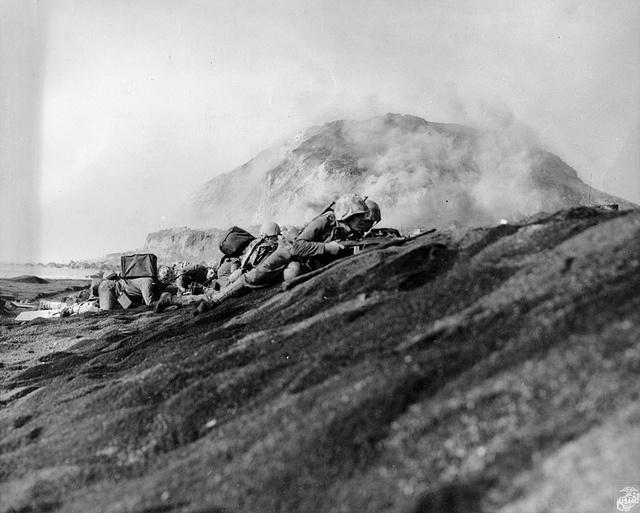 Leathernecks of the 5th Marine Division hug the beach on Iwo Jima with Mt. Suribachi in the background, February 19, 1945, one of the bloodiest battles in US Marine Corps history.