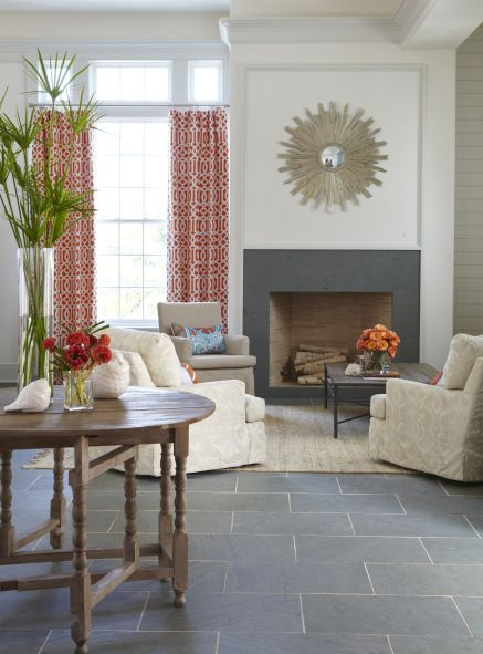 Family room: Dark gray stone floor with matching modern fireplace surround, red patterned curtains