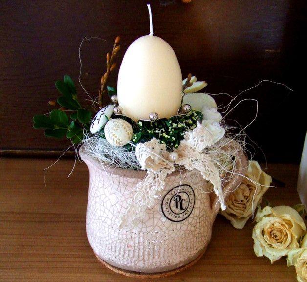 Süßes Kännchen im Shabby-Look. Verziert mit Buchs, Weidenkätzchen und einer alten Spitzenborte. Hingucker ist der schöne Kerzenhalter. Filzhase, Röschen und kleine Eier tummeln sich um die...
