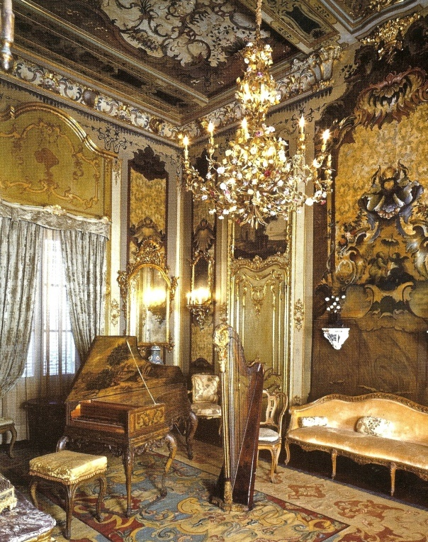 The music room in Vizcaya, Miami, FL. Cream, blue and reddish brown Aubusson rug, gold walls, chandelier.