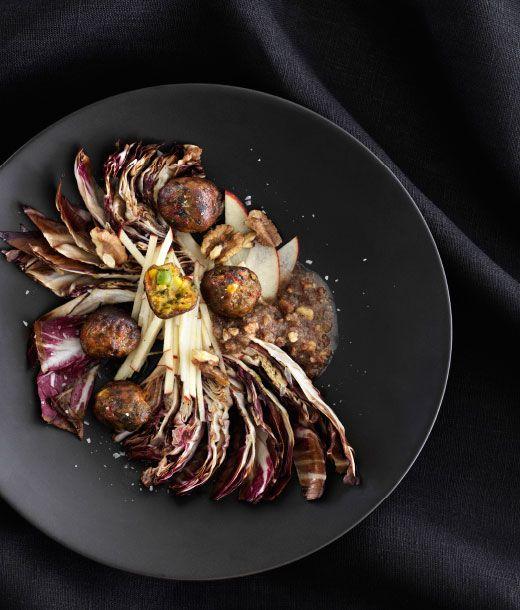 En portion varm radicchio- og valnøddesalat med IKEA grøntsagsboller på et sort fad.