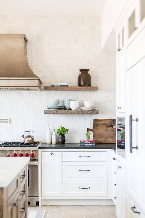 An antique nickel French vent hood is mounted to white glazed backsplash tiles beside stacked wooden shelves and above a satin nickel swing arm pot filler mounted over a Wolf dual range.