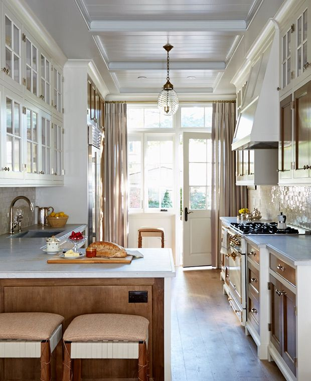 Galley kitchen - coffered, panelled ceiling, contrast between glass-paned uppers and walnut-panelled lower cabinets lends an elegant and tailored feel to the room. Palissandro marble counters and a Moroccan-tile backsplash are luxe additions, while a pretty pendant light feels like jewelry overhead.