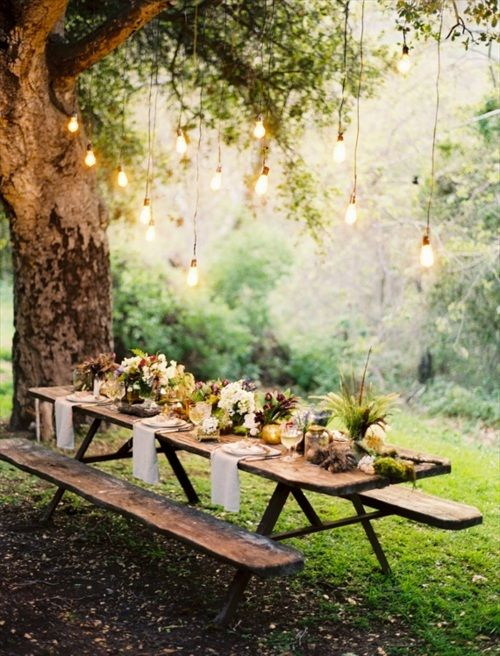 Rustic outdoor dining with hanging lights.