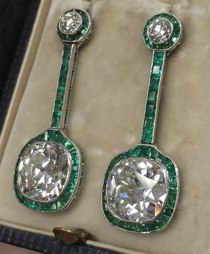 Exceptionally exquisite Art Deco diamond and emerald drop earrings, Circa 1925; Set in platinum the pair are set atop with two old European cut diamonds; total weight approx 0.80 accented with French cut Colombian emerald halo. The Emeralds cascade down highlighting a stunning matched pair of old cushion cut diamonds with a combined weight of 11 carats-weighing approx 5.50 carats each. These breathtaking earrings are beautifully accented by French cut Colombian emeralds.