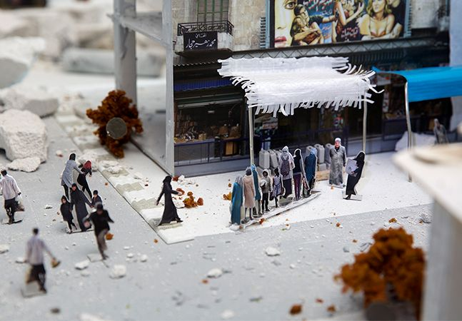 """Saskia Stolz, artista holandesa fundadora do Power of Art House, criou uma instalação interativa na Praça do Museu, em Amsterdã, onde apresenta Aleppo depois da guerra da Síria. Lançada no dia 19 de julho, exatamente 5 anos após o início dos combates, a Living Aleppo aborda o dia a dia na cidade de diversas perspectivas, mostrando como é a vida na cidade devastada pela guerra, em uma exibição instalada ao ar livre, convidando a todos que passam a parar e refletir sobre a situação. """"Vidas…"""