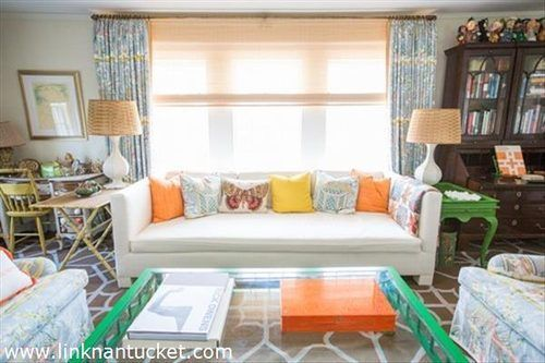 This Nantucket estate has patterned flooring, a glass coffee table, floral furniture, wooden desk with glass display, colorful pillows and patterned curtains.