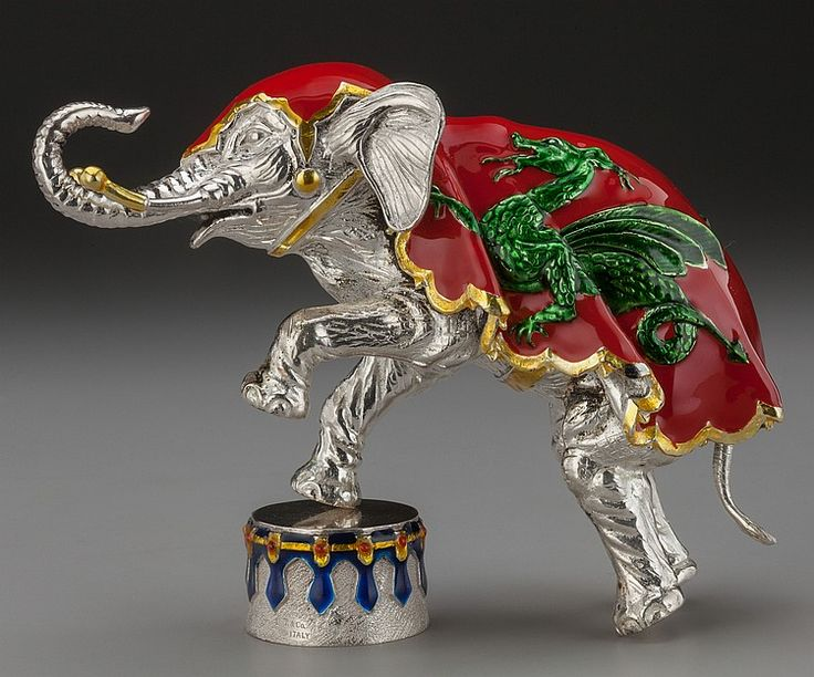 TIFFANY & CO. SILVER AND ENAMEL CIRCUS ELEPHANT AND DRUM, Designed by Gene Moore, New York, New York, circa 1990 Marks: TIFFANY & CO., STERLING, 925, MADE IN ITALY 5-1/2 inches high (14.0 cm) 26.43 troy ounces The elephant stands on hind legs and tail, with red enameled cape decorated with a dragon to either side, with a drum decorated with blue darts and yellow and red border, elephant stands independently while shown stepping on drum in image.