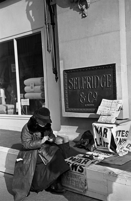 London, 1940. Life in London during The Blitz of World War II - News vendor outside Selfridges.